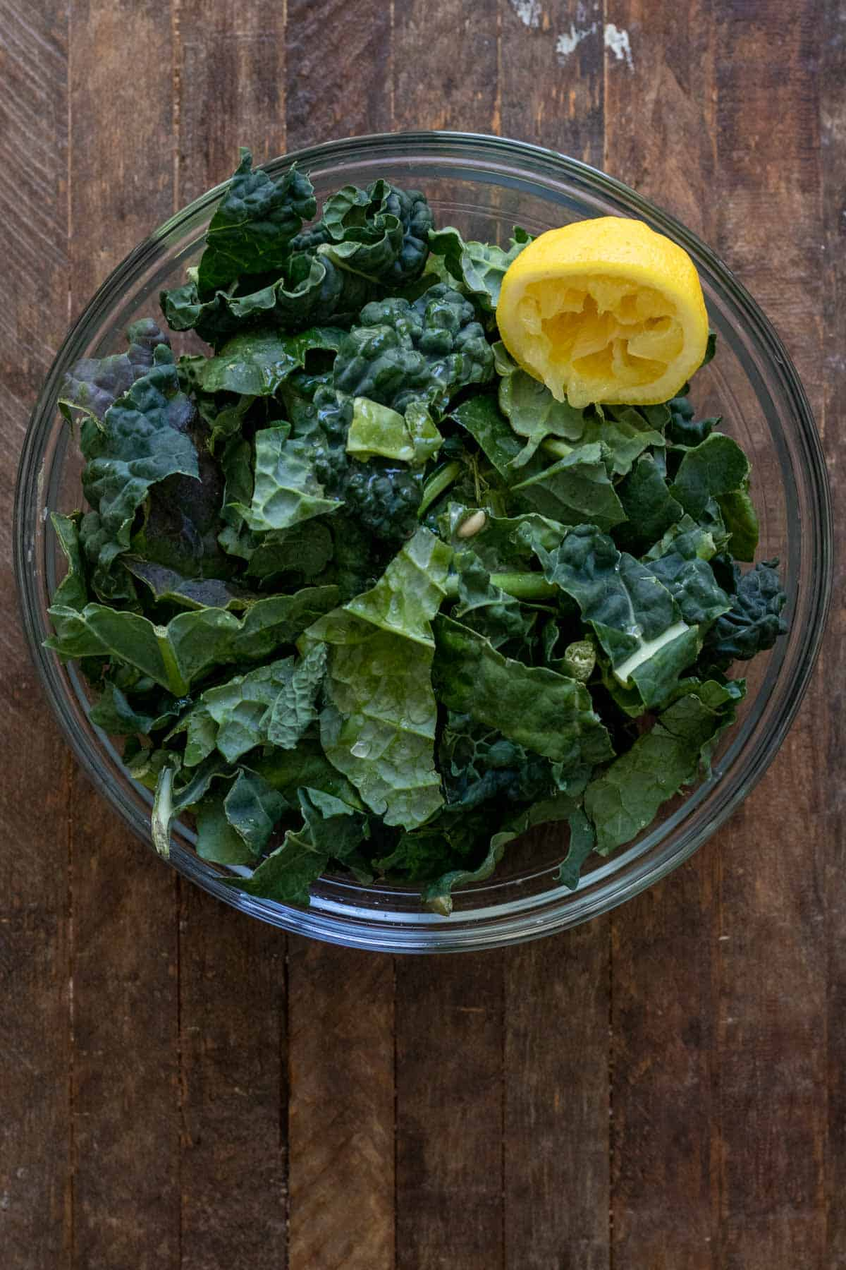 Kale in glass bowl on wooden table with lemon juice squeezed overtop.