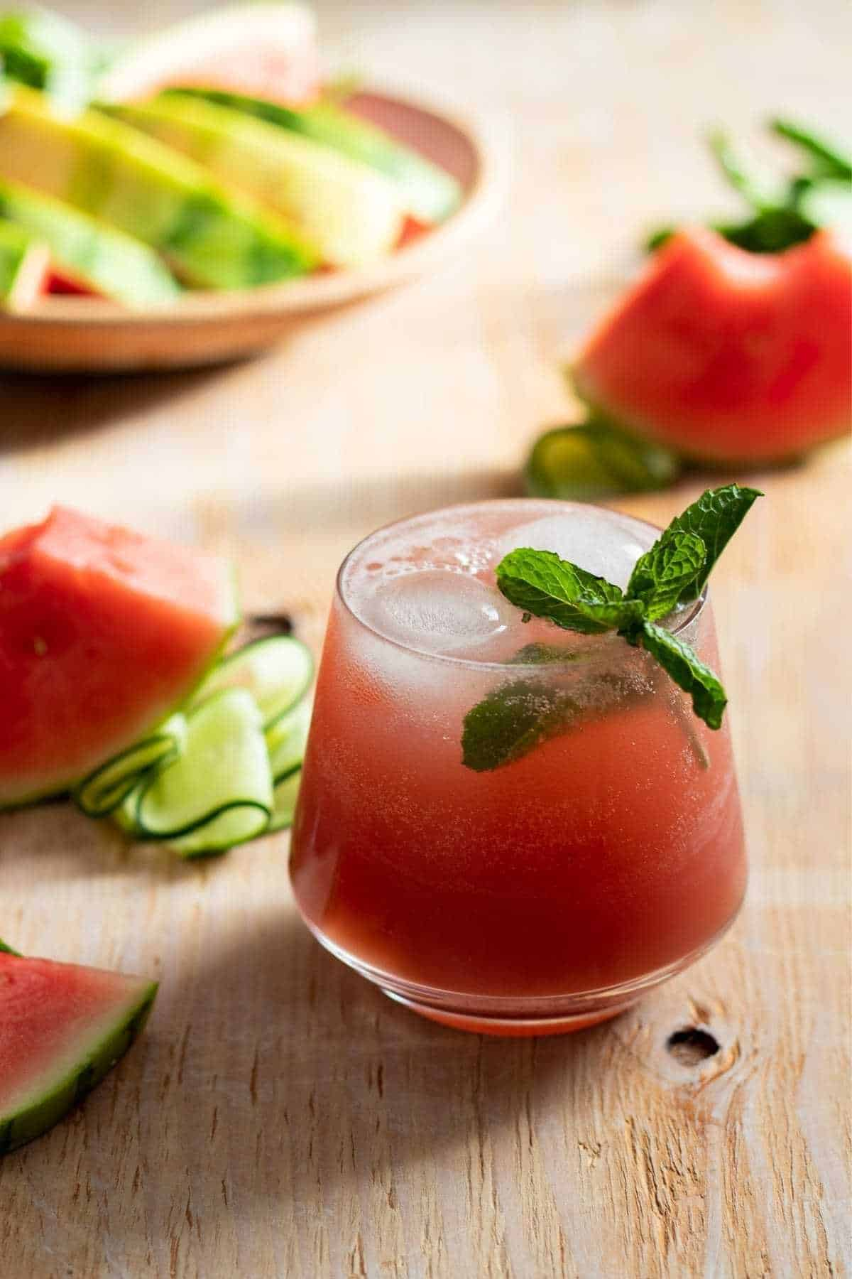 Closeup of cocktail garnished with fresh mint and watermelon wedges.