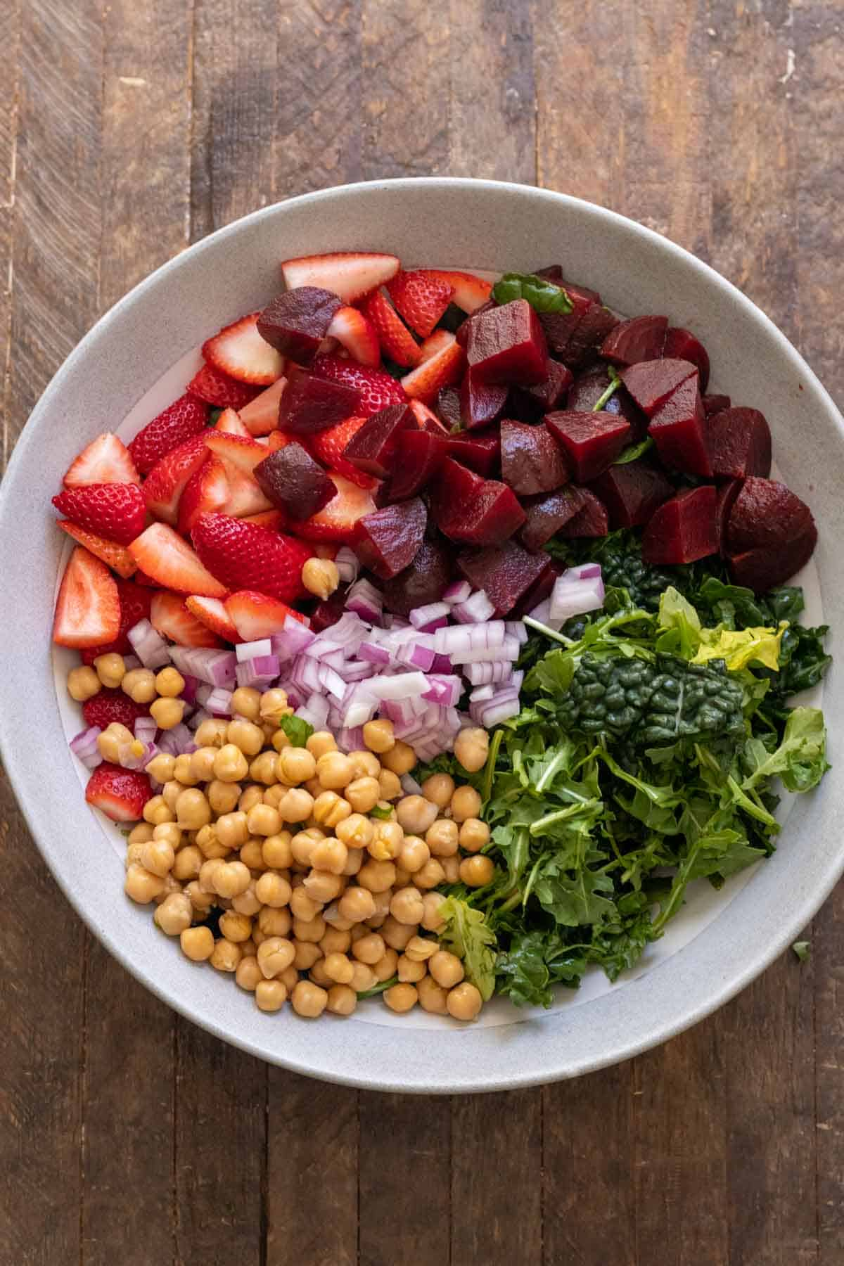 Salad ingredients layered in bowl before tossing together.