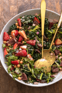 Strawberry salad in large white mixing bowl with serving utensils.