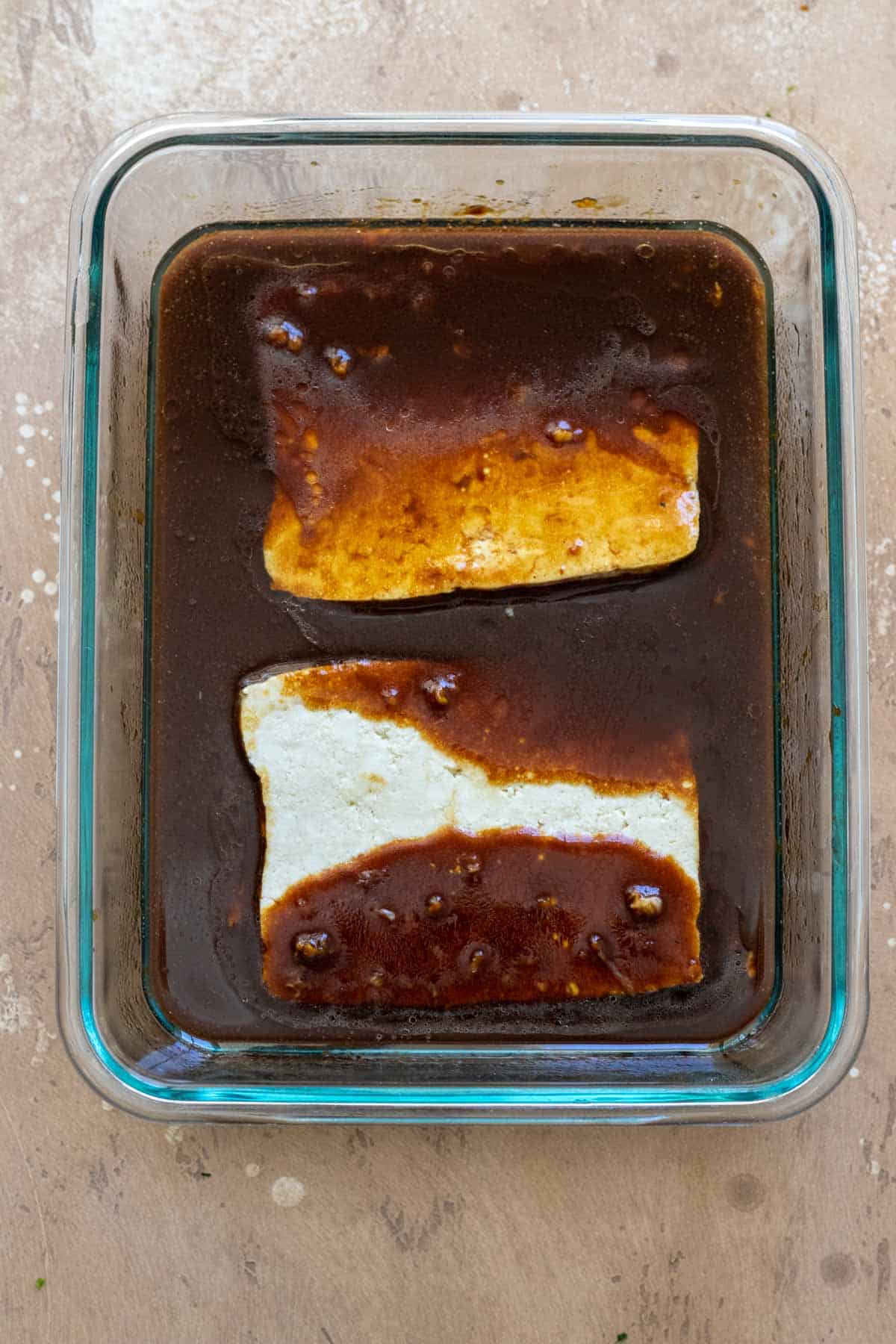 Tofu slices marinading in mixture in shallow glass dish.