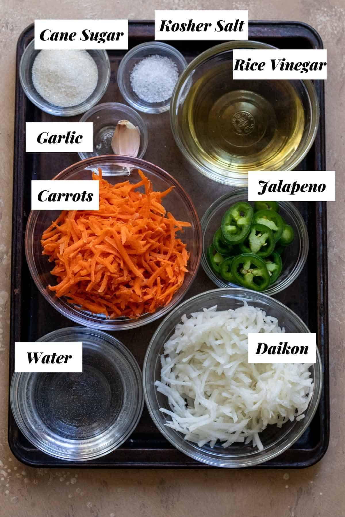 Ingredients needed to make quick pickled vegetables measured into glass bowls on cookie sheet.