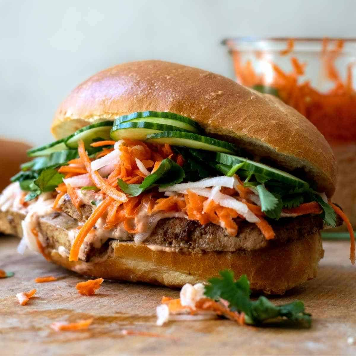 Banh mi sandwich topped with quick pickle vegetables on wooden table.