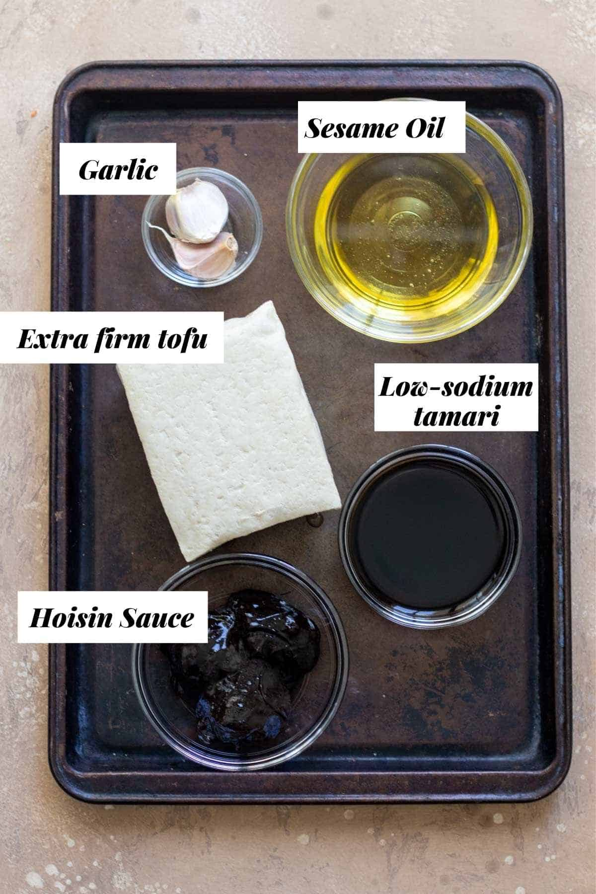 Ingredients needed to marinade the tofu for pan frying measured into glass bowls on cookie sheet.