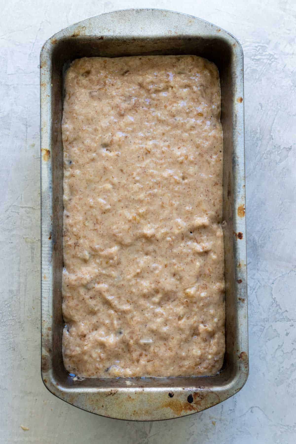 Bread batter poured into loaf pan before baking.