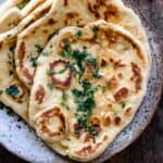 Flatbread bread pieces piled on top of one another on plate and topped with butter and chopped cilantro.