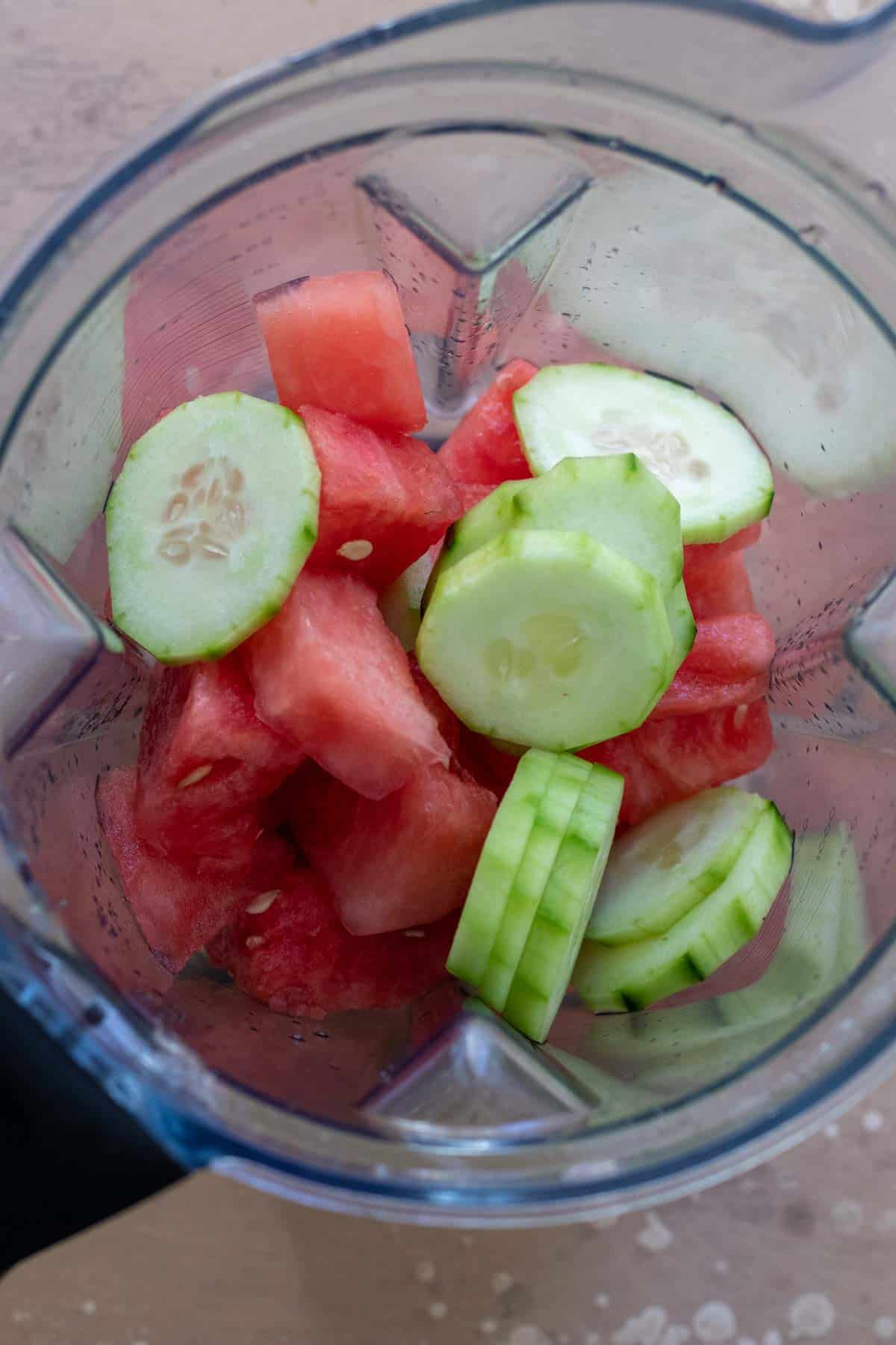 Cubed watermelon and cucumber slices in blender canister before blending.