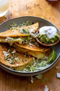 Three tacos served with shredded cabbage and sour cream and guacamole.