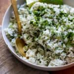 Rice in white bowl with gold spoon garnished with lime wedges.