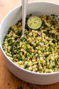 Corn salsa with half lime in large white bowl and silver spoon.