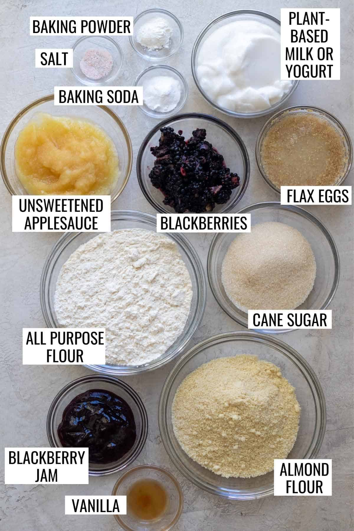 Ingredients needed for blackberry muffins measured into individual glass bowls and labeled.