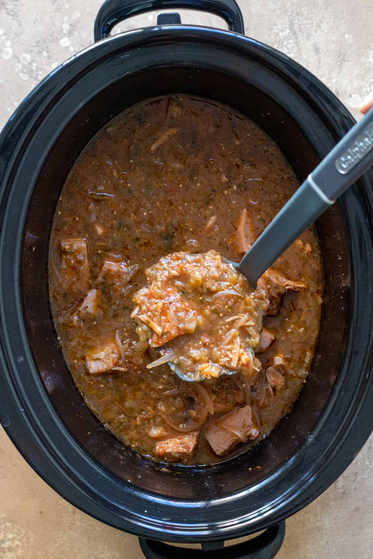 Cooked Stew in slow cooker with scoop on ladle.