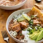 Stew topped with sour cream, avocado slices, corn chips over cilantro rice in white bowl.