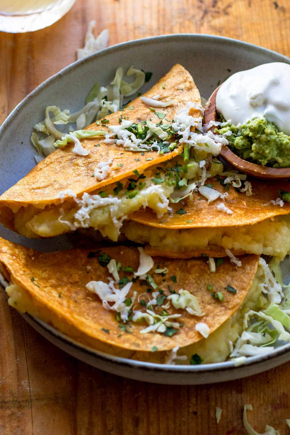Three tacos on plate topped with shredded cabbage.