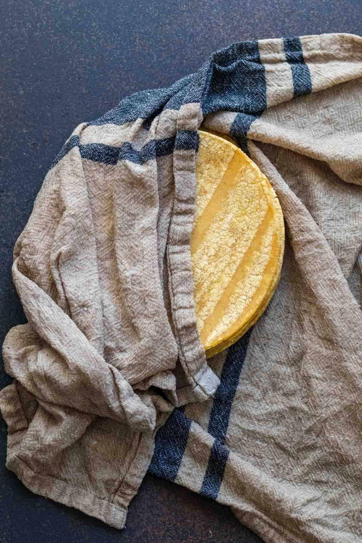Stack of corn tortillas wrapped in damp tea towel.
