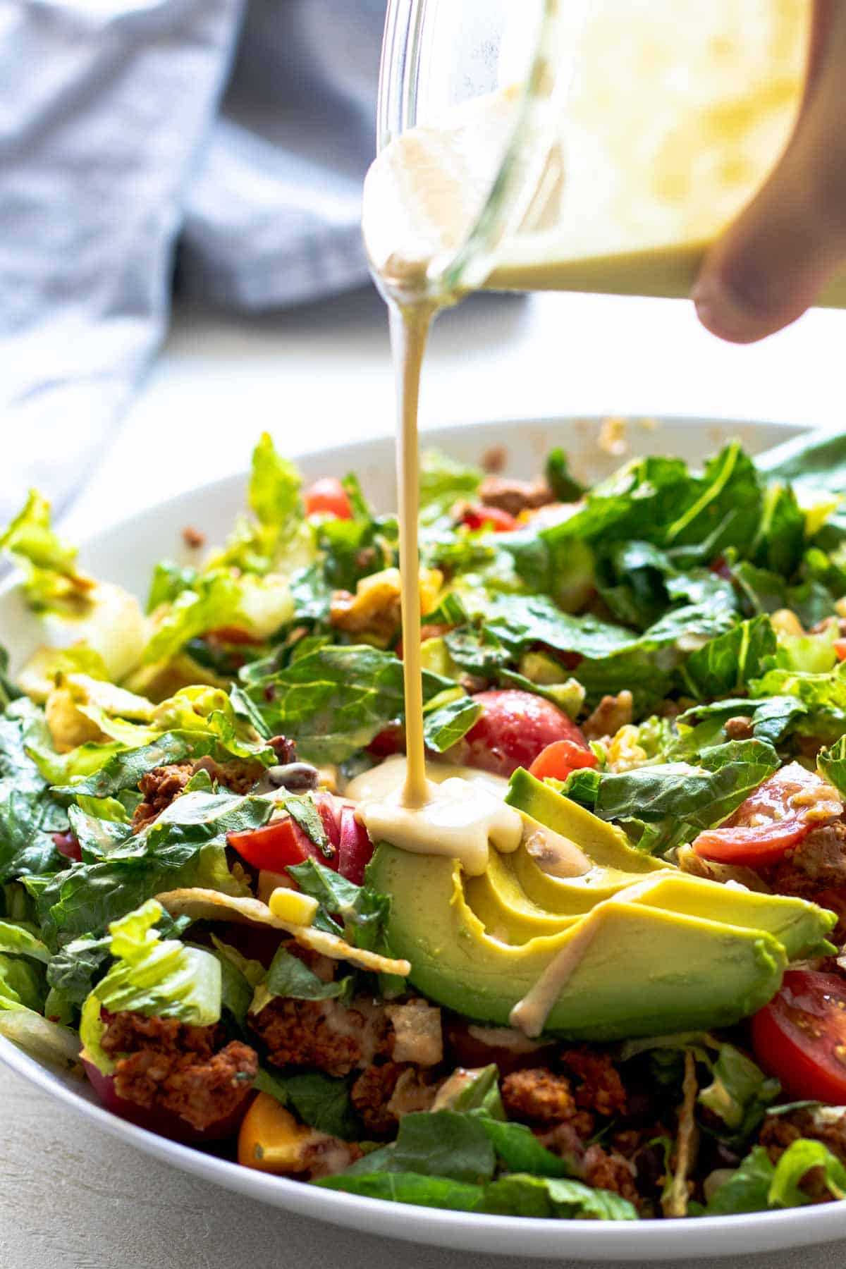 Dressing drizzled over green salad with avocado and tomatoes.