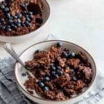 Two bowls of granola with milk and berries on blue napkin.