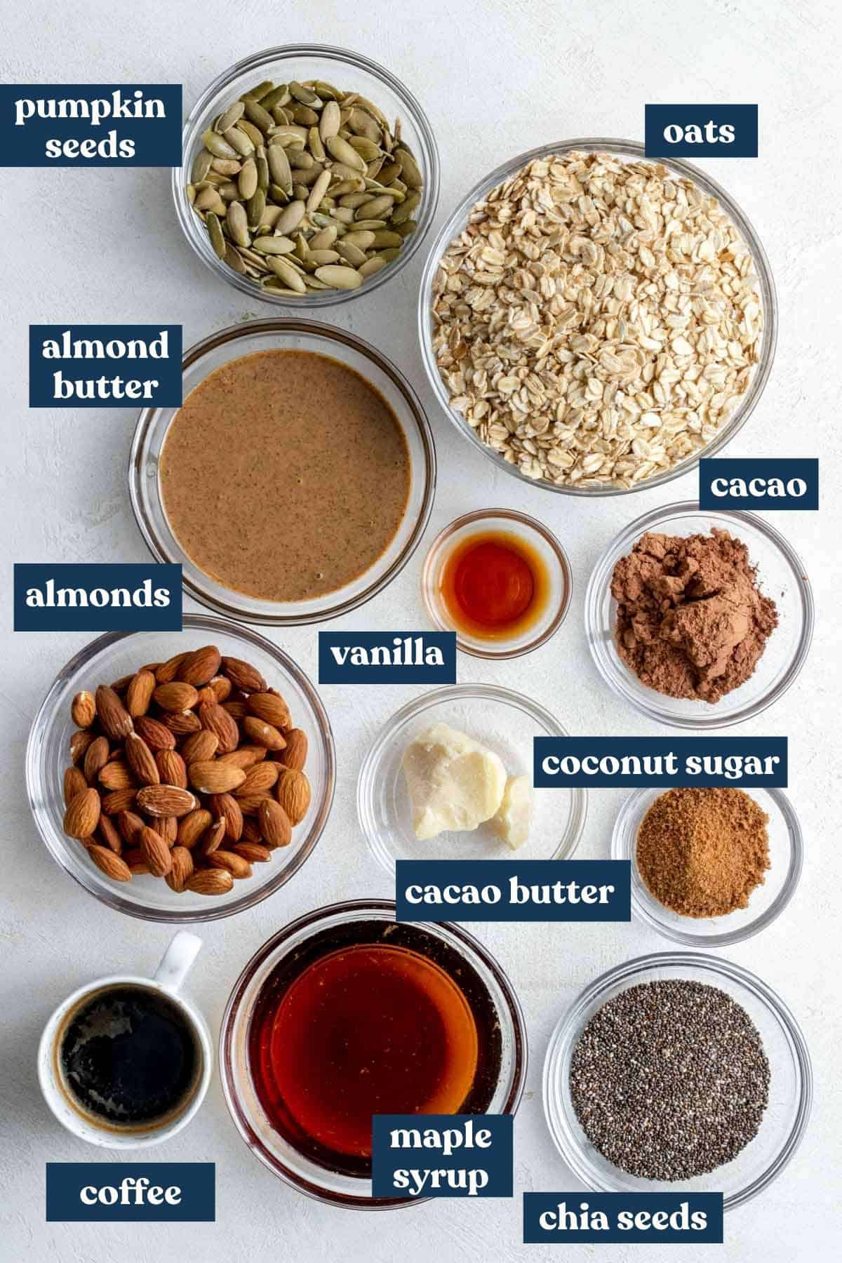 Ingredients needed for granola recipe measured into individual bowls and labeled.