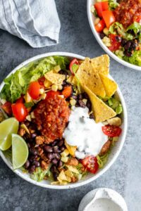 Taco salad bowl garnished with salsa and lime wedges in white bowl.