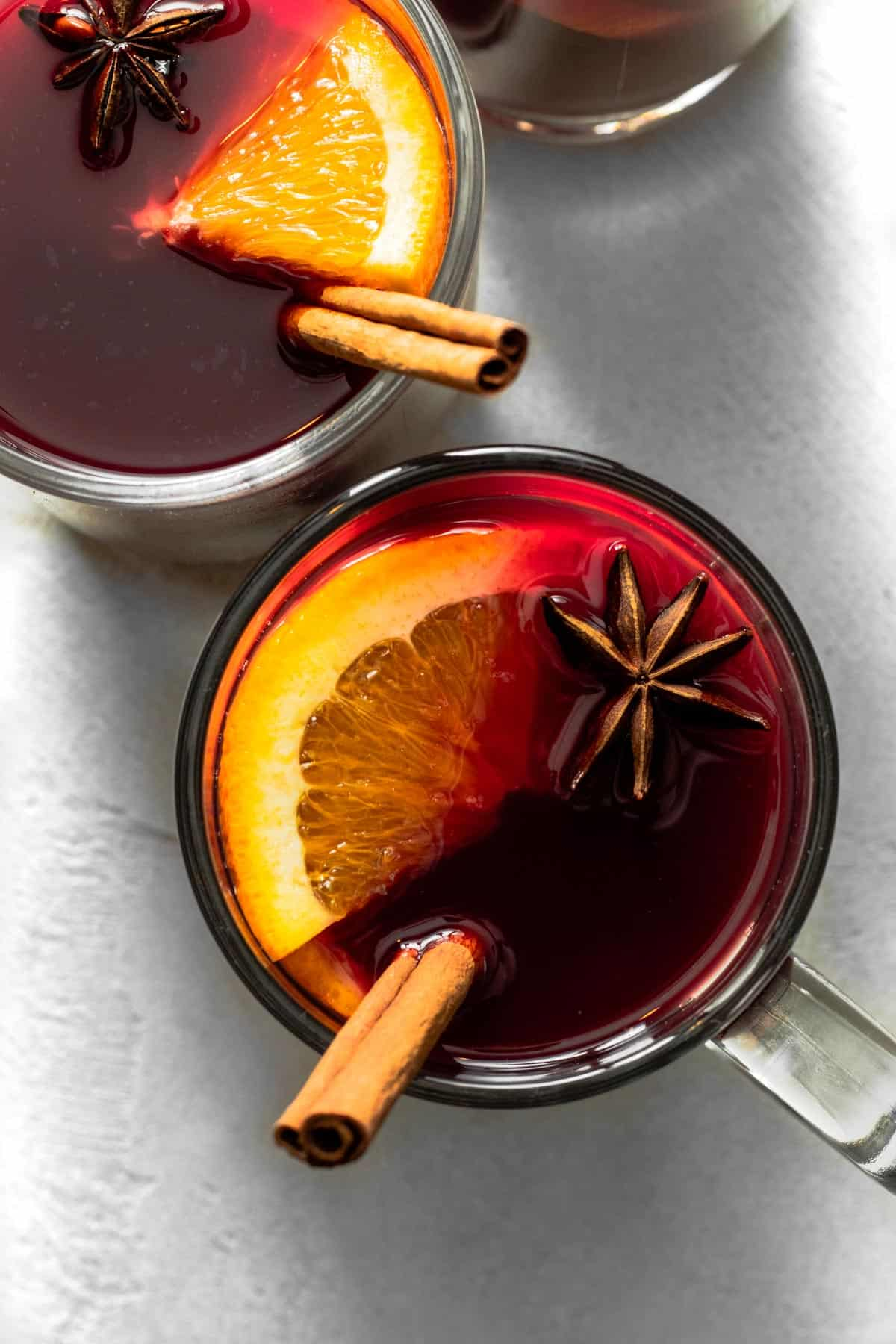 Non-alcoholic mulled wine in mug garnished with orange slice, star anise, and cinnamon.