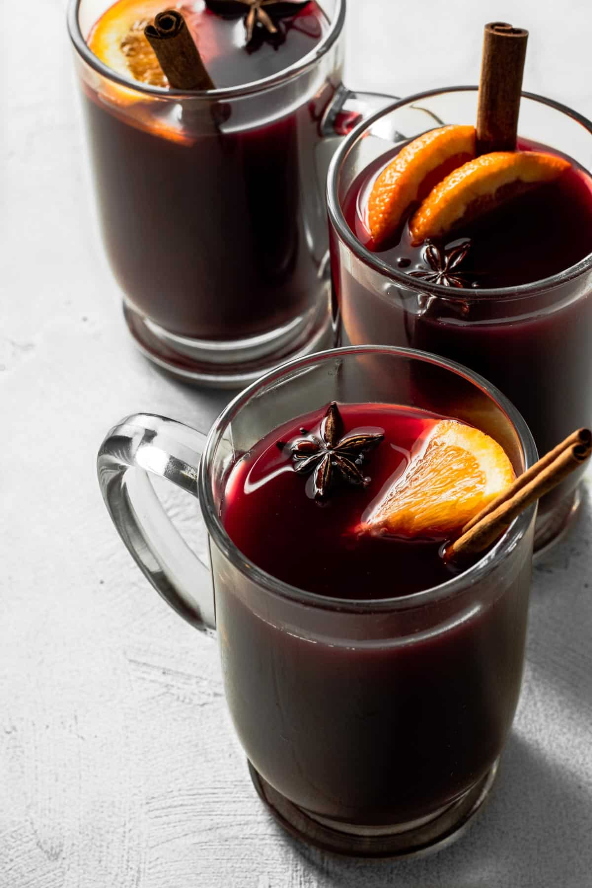 3 glass mugs full of non-alcoholic mulled wine on gray background.
