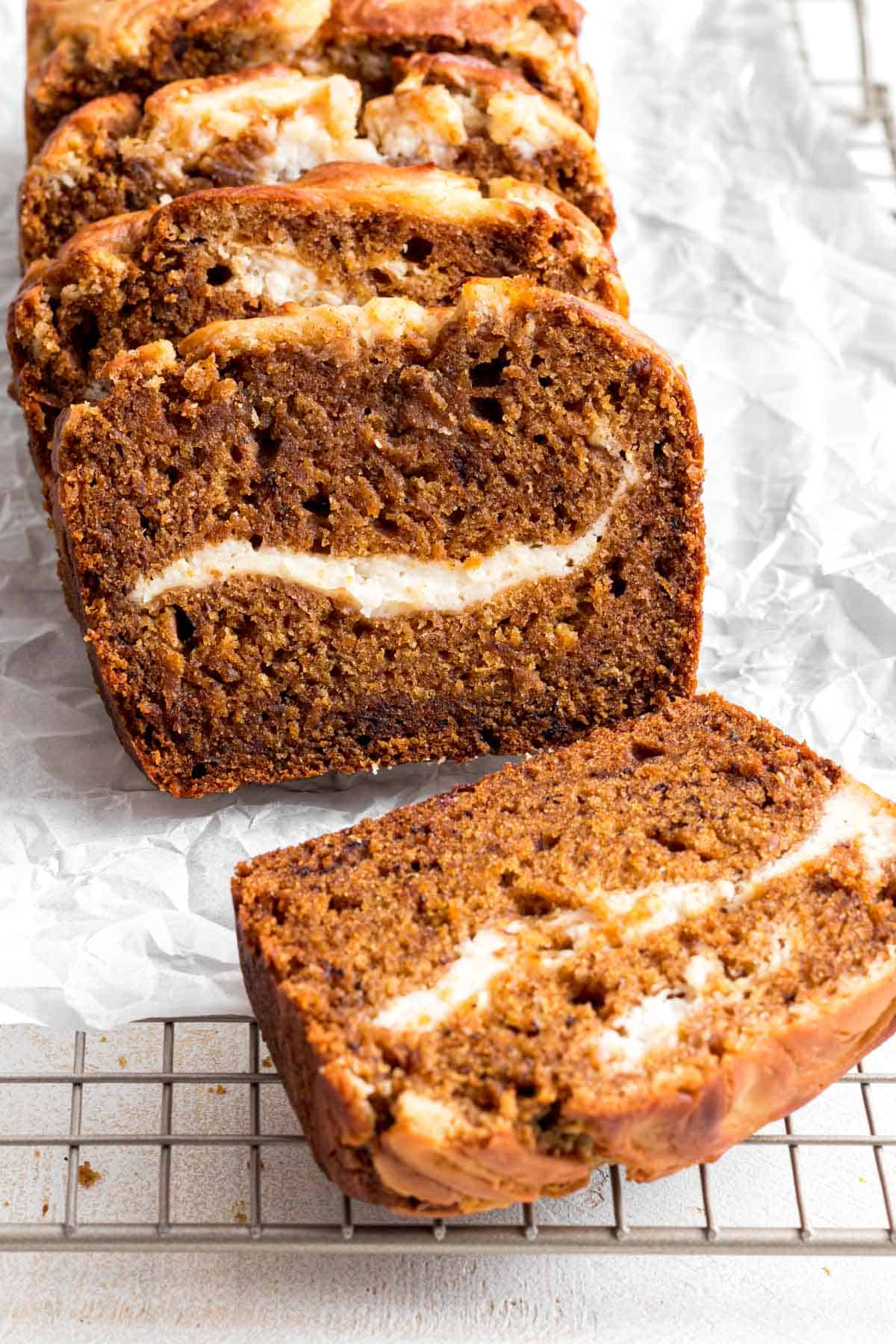 Slices of pumpkin banana bread on white parchment paper and cooling rack.